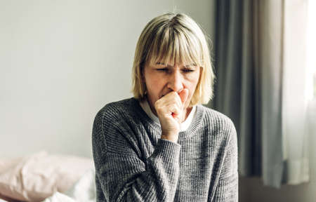 Sick senior adult elderly asia women feeling unwell coughing with sore throat.Healthcare and medicine concept Standard-Bild
