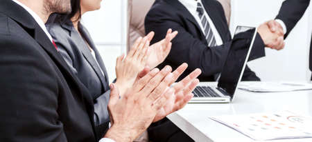 Image two business partners in elegant suit successful handshake together in front of group of casual business clapping hands in modern office.Partnership approval and thanks gesture concept Foto de archivo