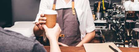 Woman barista giving coffee cup to customer at cafe 版權商用圖片