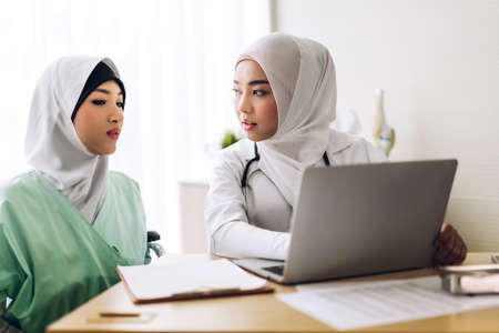 Muslim asian female doctor consulting and check up information on laptop computer with muslim woman in hospital.woman has sick.healthcare and medicine