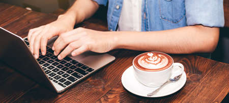 Woman drinking coffee and work on laptop computer at coffee shop