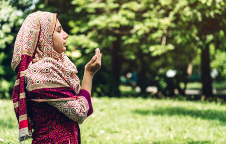 Religious muslim asian woman praying hands on park background Stok Fotoğraf