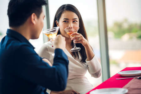 Romantic young happy couple relax talking and drinking wine glasses celebrate together in the restaurant