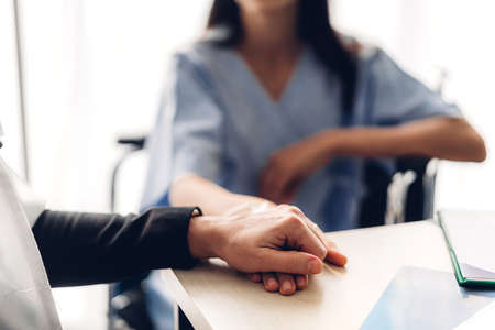 Woman doctor consulting and holding hand patient reassuring with care on doctors table in hospital.healthcare and medicine Reklamní fotografie