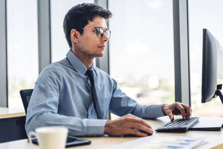 Handsome businessman relaxing using desktop computer while sitting on chair.creative business people working and management at modern office 版權商用圖片