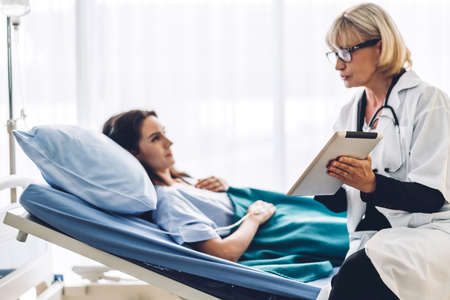Doctor discussing and consulting check up information on tablet computer with female patien on the bed in hospital.healthcare and medicine 版權商用圖片