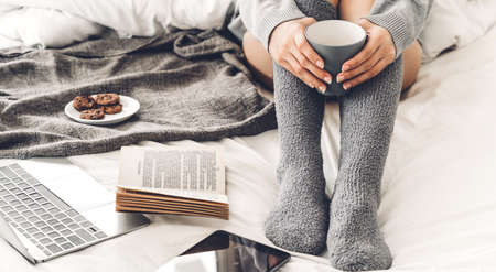 Young woman relaxing and drinking cup of hot coffee or tea  on a cold winter day in the bedroom