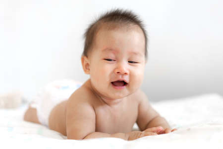 Portrait of happy asian smile baby relaxing on the bed Reklamní fotografie