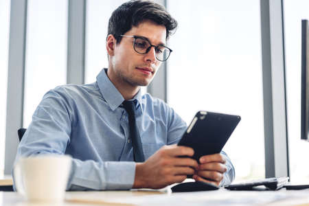 Handsome businessman relaxing using tablet computer while sitting on chair.creative business people working and planning at modern office 版權商用圖片