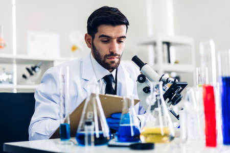 Professional scientist man doing a chemical experiment while making a research and using microscope with mixing chemicals in test tube at modern Laboratory