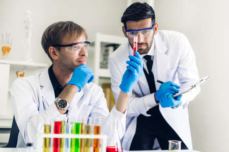 Professional scientist man doing a chemical experiment while making a research with mixing chemicals in test tube at modern Laboratory