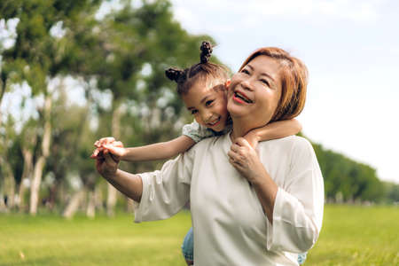 Portrait of happy grandmother and little cute girl enjoy relax together in summer park.Family and togetherness