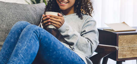 Young african american black woman relaxing drinking cup of hot coffee or tea on couch at home 版權商用圖片