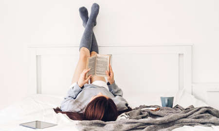 Young woman relaxing reading book and drinking cup of hot coffee or tea  on bed at home 版權商用圖片