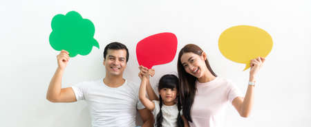 Happy family father and mother with daughter holding a speech bubble icon