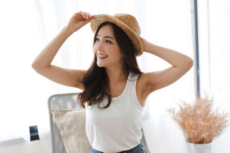 Portrait of asia fashion style smilling beautiful woman model posing in room at home