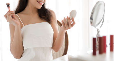Smiling young beautiful woman fresh healthy skin looking on mirror with makeup cosmetics set at home.facial beauty and cosmetic concept