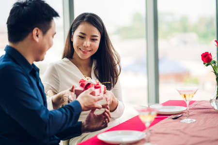 Young handsome man giving gift box surprise to girlfriend