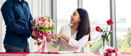 Young handsome man giving red rose surprise to girlfriend and holding flower in valentine day at home