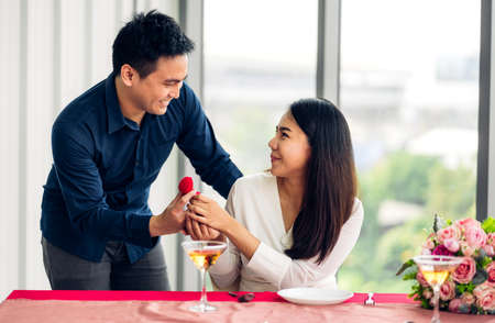 Young handsome man giving red rose surprise to girlfriend and holding flower in valentine day at home 版權商用圖片 - 162325676