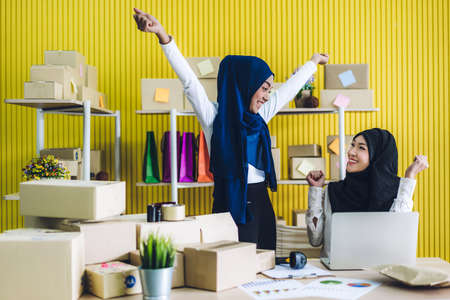 Muslim two asian woman freelancer sme business online shopping working on laptop computer with cardboard box on table at home - Business online shipping and delivery concept