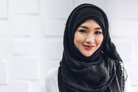 Portrait of happy arabic muslim woman with hijab dress smiling and look at camera on white wall background Foto de archivo