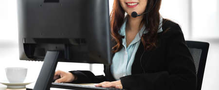 Beautiful happy smiling businesswoman operator customer support phone services working with headset and computer at call center