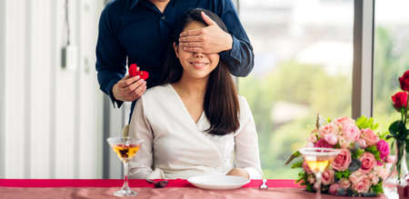 Young handsome man giving ring for surprise to girlfriend and talking together in the restaurant Foto de archivo