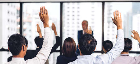 Businessman standing in front of group of people in consulting meeting conference seminar and showing hand to answer question at hall or seminar room.presentation and coaching concept Foto de archivo