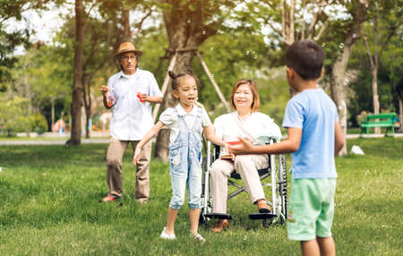Portrait of happy grandfather with grandmother and little cute girl enjoy relax in summer park.Young girl with their laughing grandparents smiling together.Family and togetherness