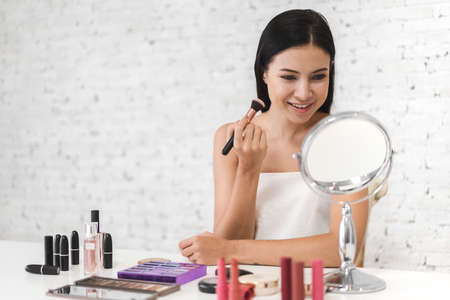 Smiling of young beautiful pretty woman clean fresh healthy white skin looking at mirror.girl holding make-up brushes and make up on face with cosmetics set at home.facial beauty and cosmetic concept