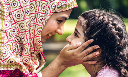 Portrait of happy lovely family arabic muslim mother and little muslim girls child with hijab dress smiling and having fun kissing together in summer park