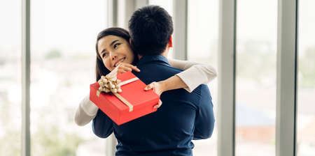 Young handsome man giving gift box surprise to girlfriend.Beautiful smiling woman hugging man at home