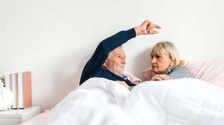 Senior happy couple relaxing and talking together lying on bed in bedroom at home.Retirement couple concept