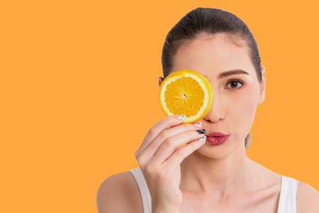 Portrait of beautiful joyful young pretty cute happy asian woman holding juicy orange fruit slice hiding eye behind and looking at camera isolated on orange background.Healthy food eating concept.Diet Foto de archivo