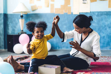 African american mother playing with adorable little african american girl at home.Love of black family concept Foto de archivo