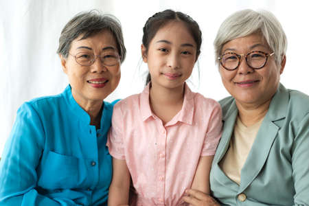 Portrait of happy asian grandmother and little cute girl enjoy relax together look at camera.Family and togetherness
