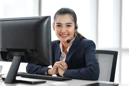 Beautiful happy call center smiling businesswoman operator customer support phone services working with headset and computer at call center