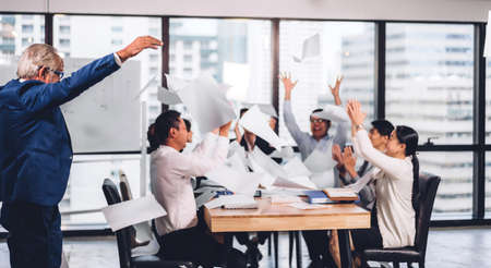 Successful group of casual business relaxing and throwing paper in modern work loft.Creative business people celebrating with arms up.Teamwork and success concept Foto de archivo