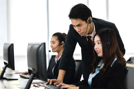 Group of happy smiling business operator customer support team phone services working with headset and computer at call center