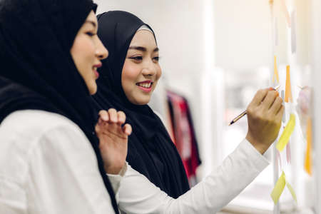 Two muslim business woman planning and brainstorm writing over the project with stickers note on glass window at modern office.Teamwork concept 版權商用圖片