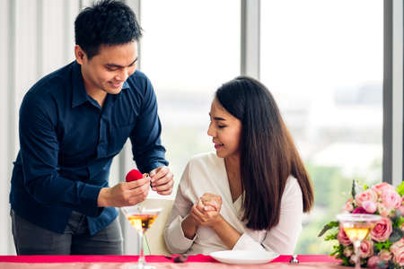 Young handsome man giving ring for surprise to girlfriend and talking together in the restaurant 版權商用圖片