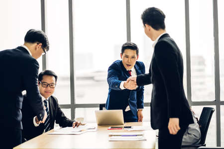 Image two business partners in elegant suit successful handshake together with meeting  group of casual business in modern office.Teamwork concept