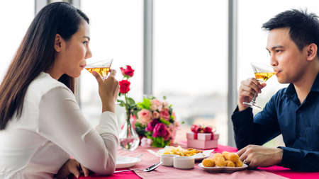Romantic young happy couple relax talking and drinking wine glasses celebrate together in the restaurant 版權商用圖片 - 161948379