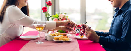 Beautiful couple in love and enjoying together eating meal sitting in the Restaurant Foto de archivo