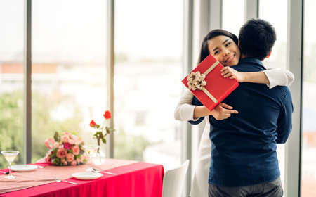 Young handsome man giving gift box surprise to girlfriend.Beautiful smiling woman hugging man at home 版權商用圖片 - 161948385