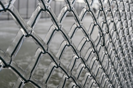 implications: Background. Metal grid in ice. In winter, the rain and froze on the fence mesh.