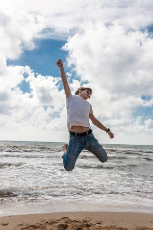 beach hunk: Young man jumping on the beach in the oncoming waves. Stock Photo