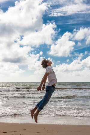 Young man jumping on the beach in the oncoming waves. Stock Photo