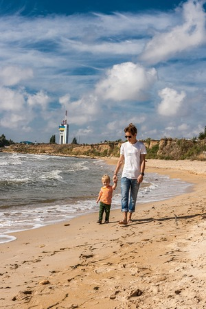 Happy elder brother leads his younger brother by the hand along the beach. Coast of Black sea Ukraine. Stock Photo